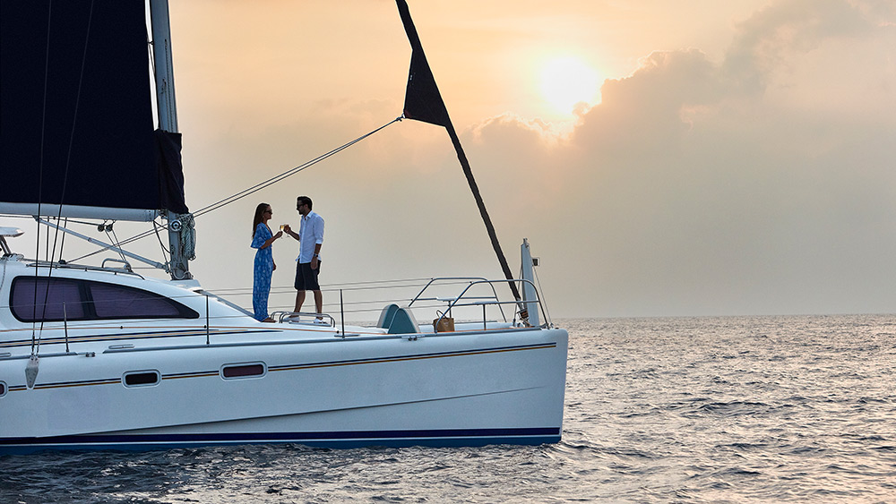 Couple on a catamaran at sunset at One&Only Reethi Rah