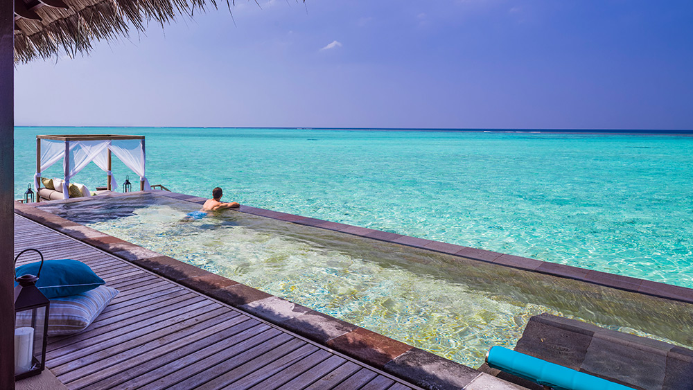 Man in the private pool of the Water Villa with Pool at One&Only Reethi Rah
