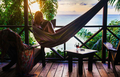 Woman in a hammock on the balcony at Cocos Hotel