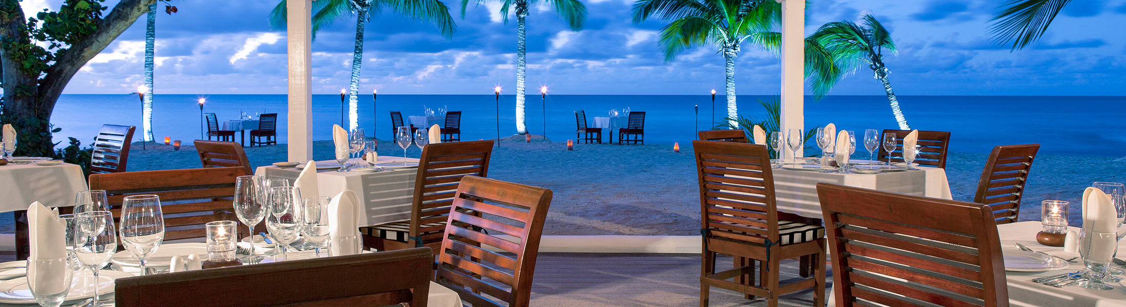 Outdoor dining at sunset at Galley Bay Resort & Spa