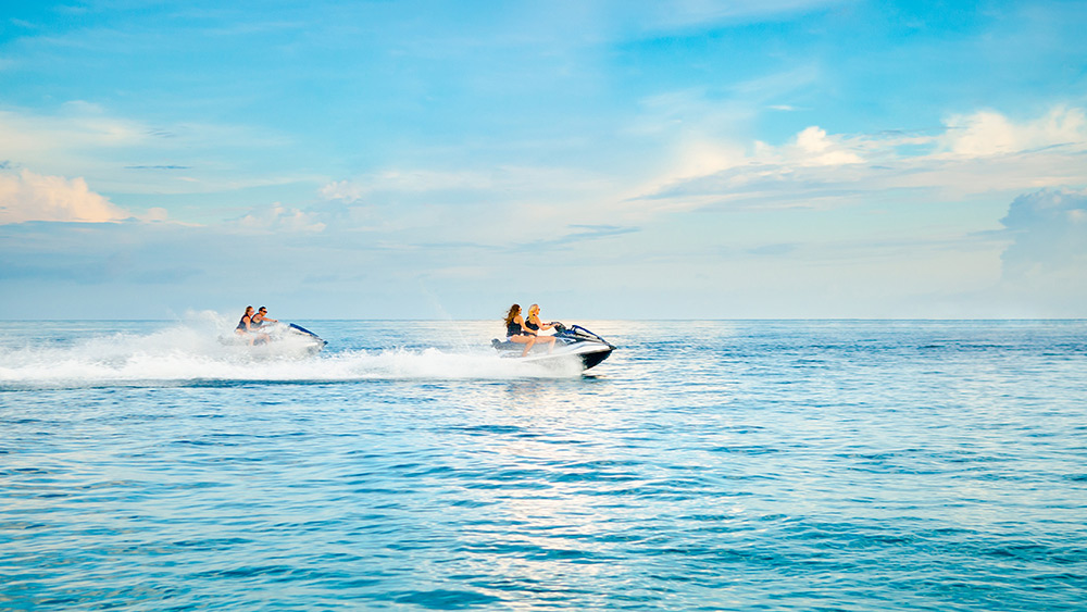 Couples riding jet skis at One&Only Reethi Rah