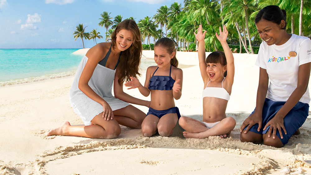 Mother and children on the beach at One&Only Reethi Rah