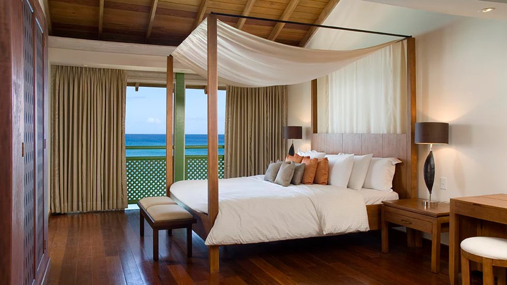 Bedroom with four post bed in the Penthouse at Mango Bay