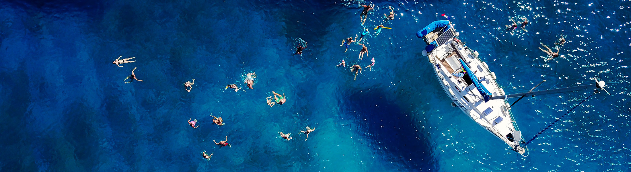 Aerial view of a catamaran and swimmers at Mango Bay in Barbados
