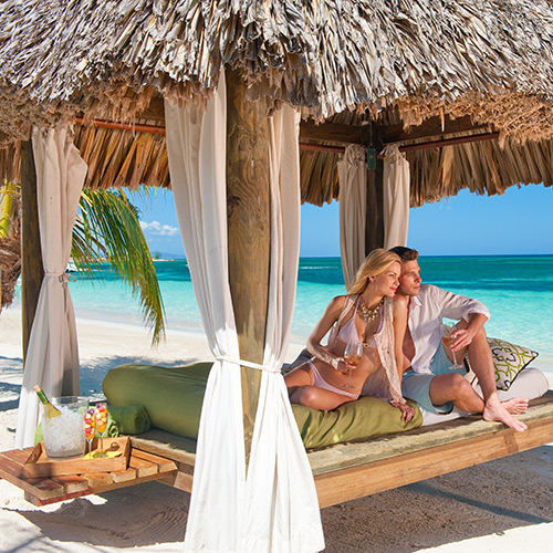 Couple in a cabana on the beach at Sandals Montego Bay
