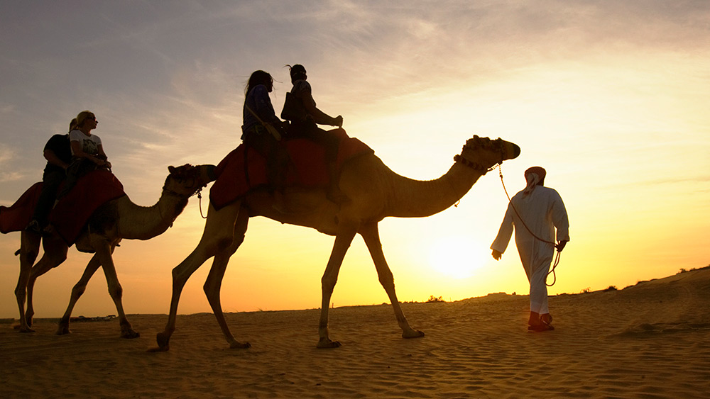 Couple riding a camel at sunset at One&Only Royal Mirage The Palace