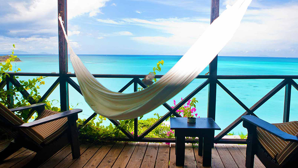 Hammock on the balcony of the Sunset View Cottage at Cocos Hotel