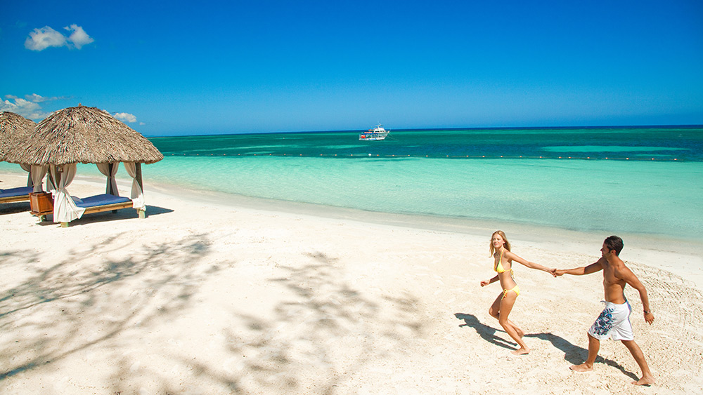 Couple walking on the beach at Sandals Montego Bay