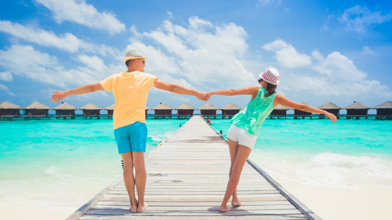 Couple holding hands on a jetty in the Maldives