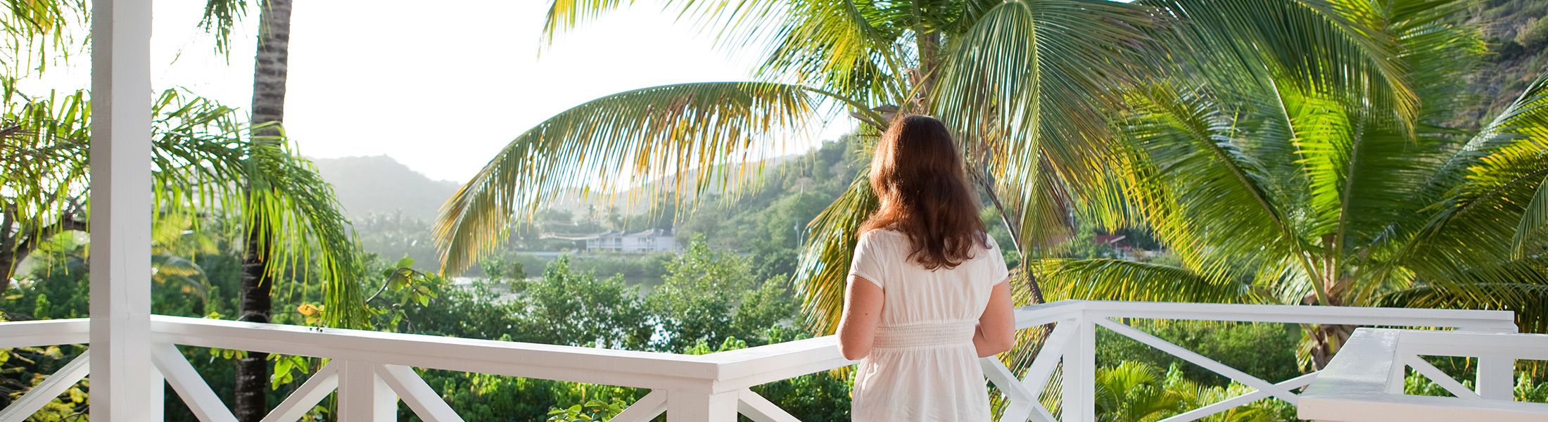 Woman on a balcony overlooking tropical gardens in Antigua