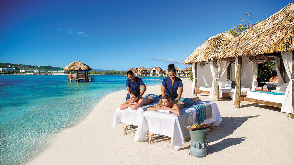Couple getting a massage on the beach at Sandals Royal Caribbean