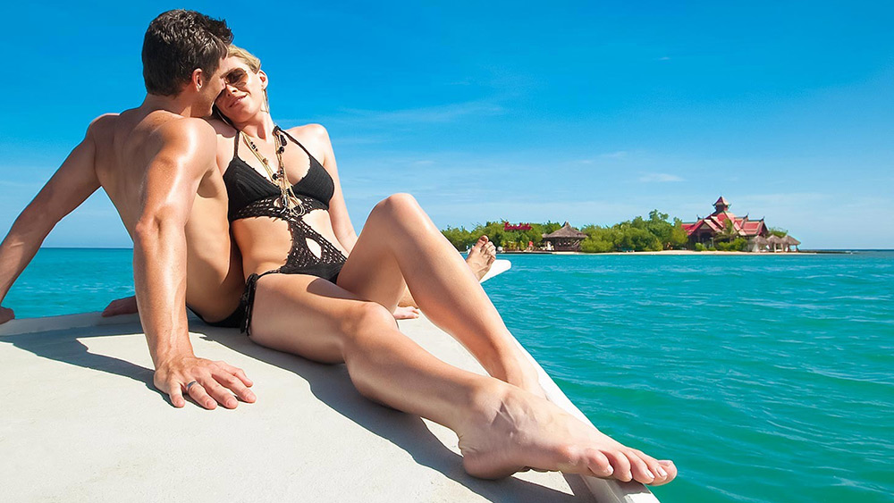 Couple in swimmers on a boat at Sandals Royal Caribbean
