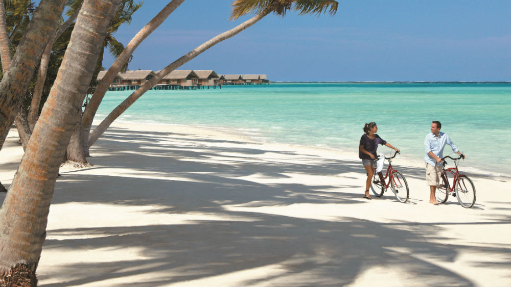 Couple cycling on the beach at the Shangri La Villingili Maldives