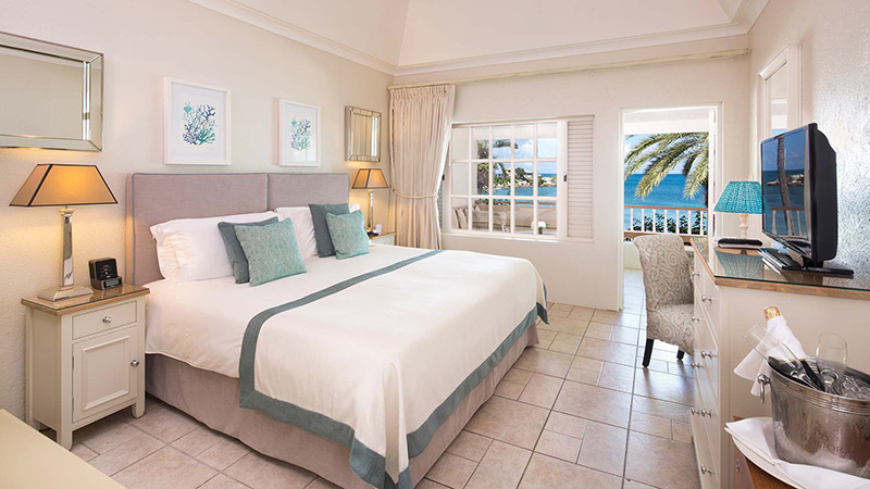 Bedroom of the Deluxe Beachfront Room at Blue Waters Resort in Antigua