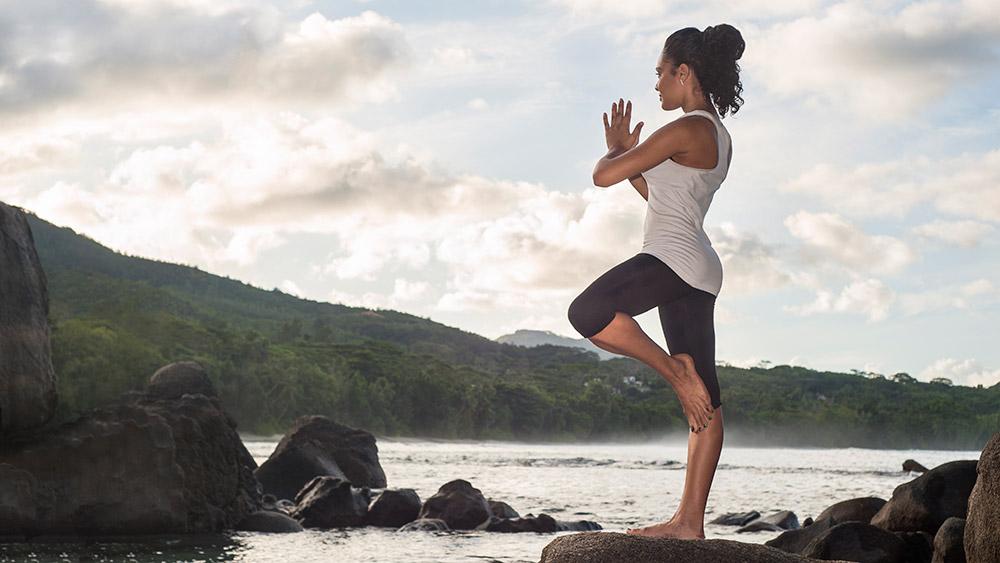 Woman doing yoga at AVANI Barbarons Seychelles