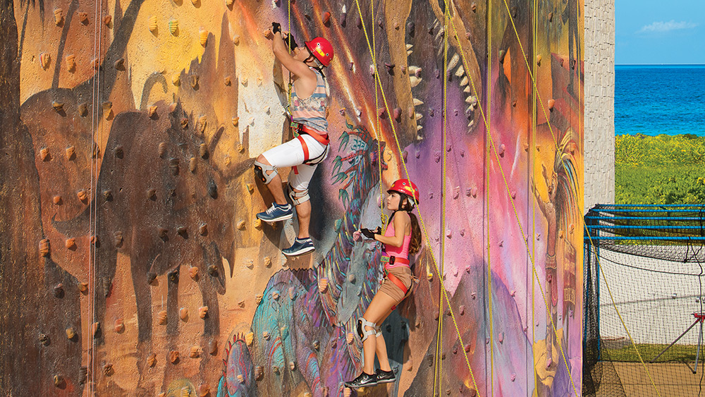Couple on a climbing wall at Dreams Playa Mujeres