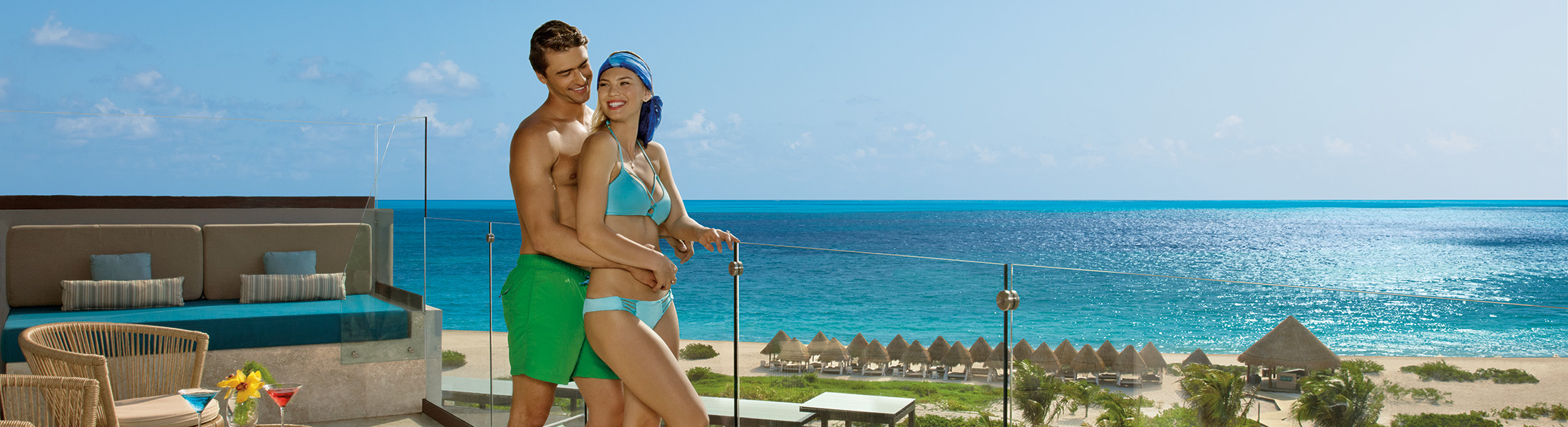 Couple on the balcony with ocean views at Dreams Playa Mujeres