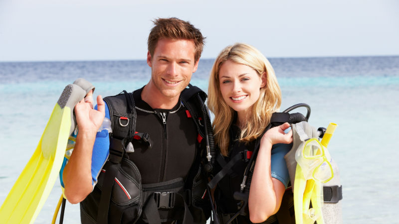 Couple With Scuba Diving Equipment Enjoying Beach Holiday