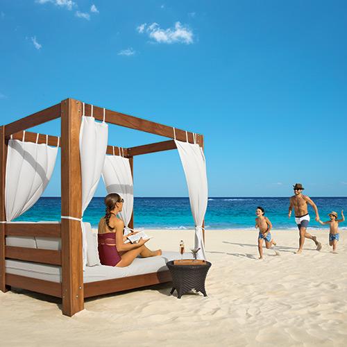 Family on a beach cabana at Dreams Riviera Cancun