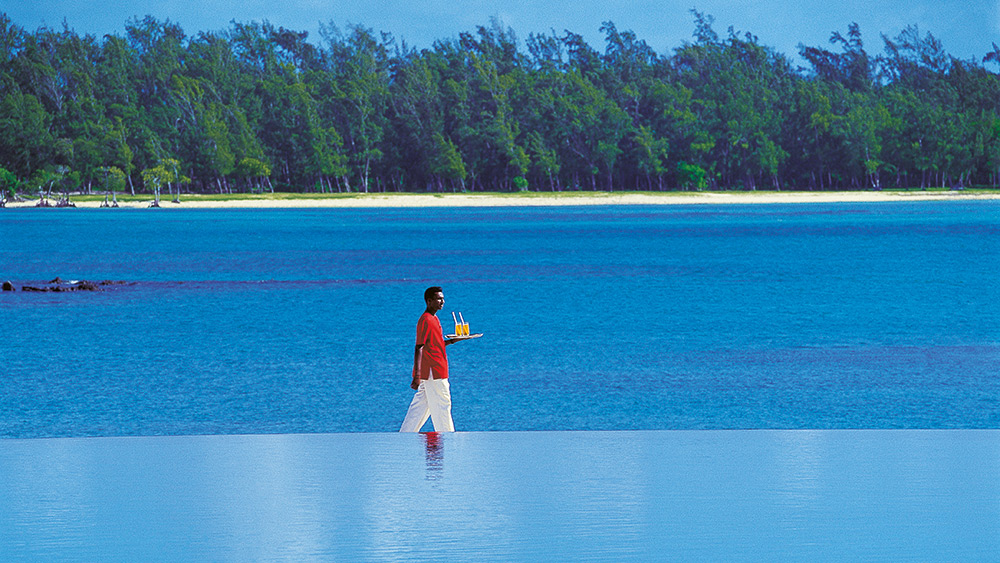 Waiter delivering drinks behind an infinity pool at Constance Prince Maurice