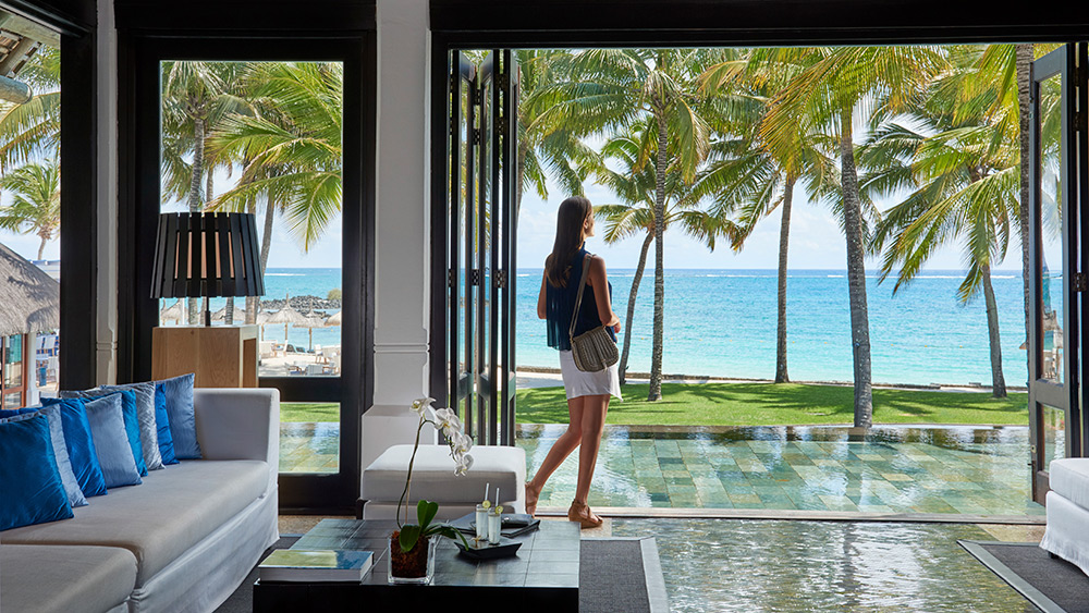 Woman in the lobby at Constance Belle Mare Plage with a view of the ocean