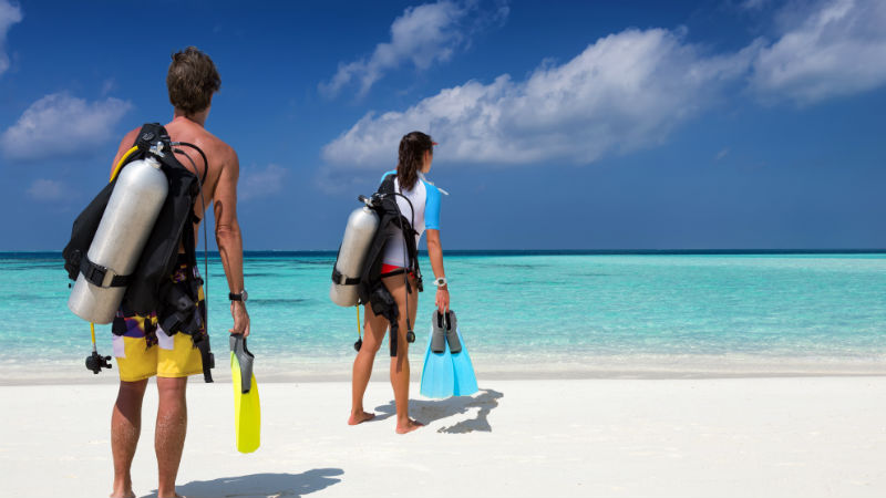 Scuba diver couple with diving equipment on the beach