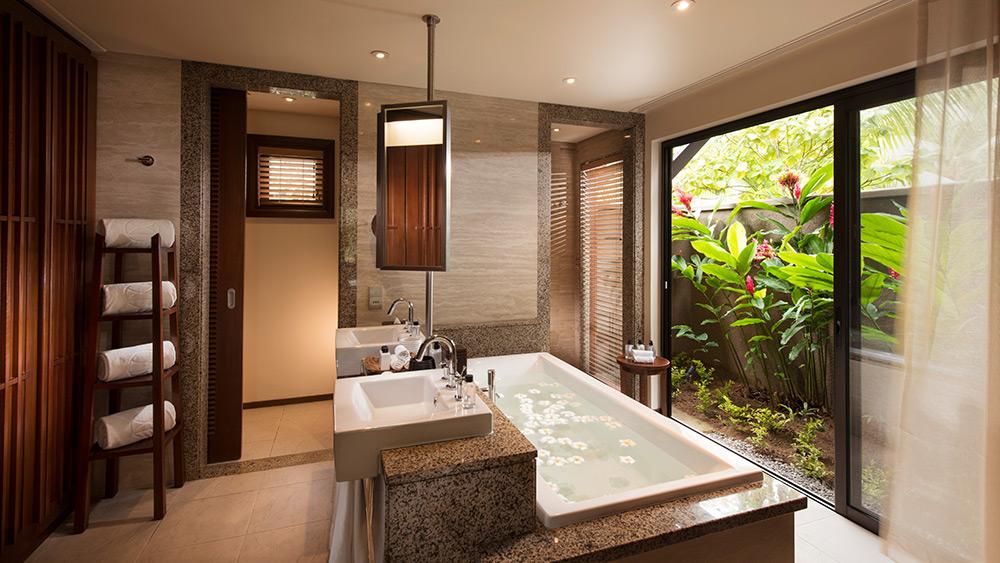 Spa bath overlooking tropical garden in the Senior Suite at Constance Ephelia