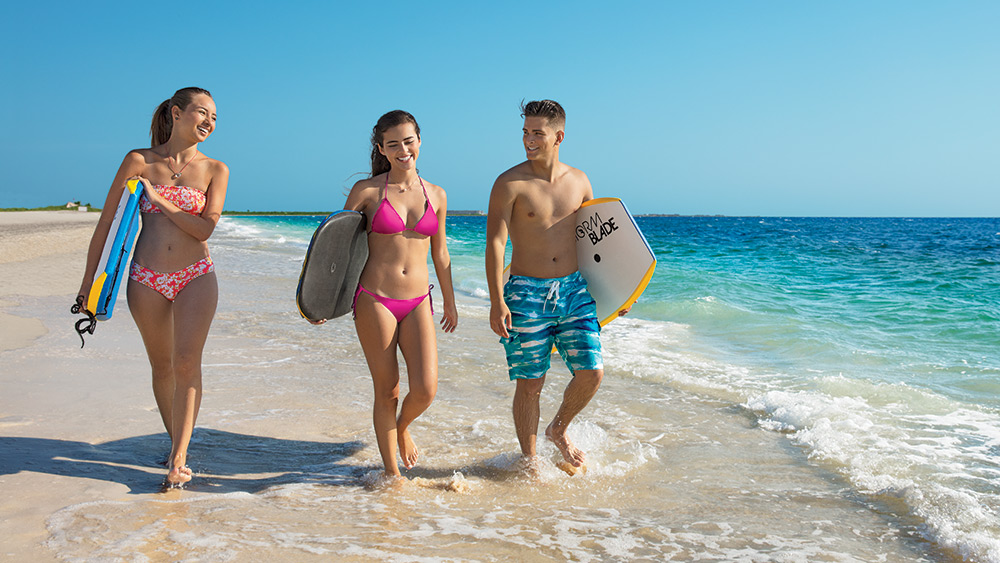 teens with boogie boards on the beach at Dreams Playa Mujeres