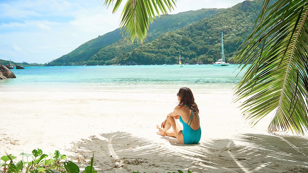 Woman sitting on the beach at Constance Ephelia