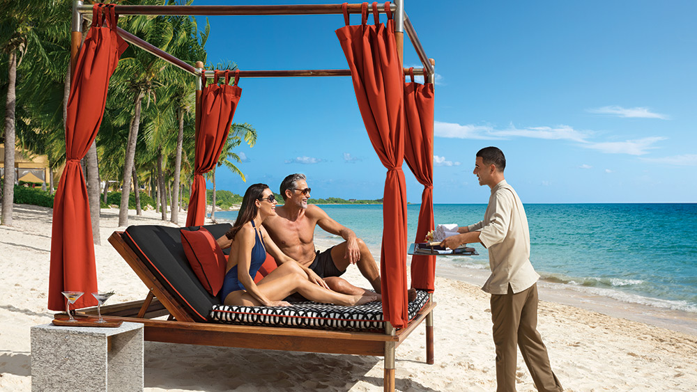 Couple being served drinks in a beach cabana at Zoetry Paraiso de la Bonita