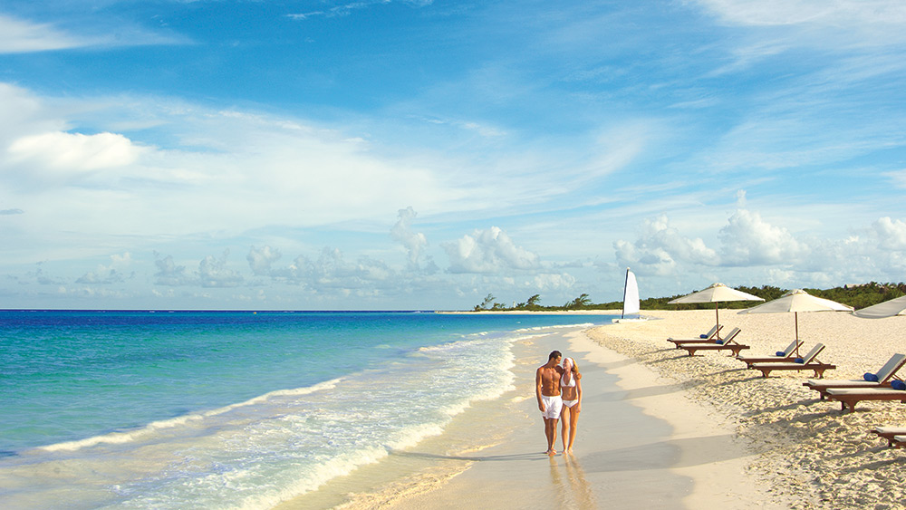 Couple walking on the beach at Secrets Maroma Beach Riviera
