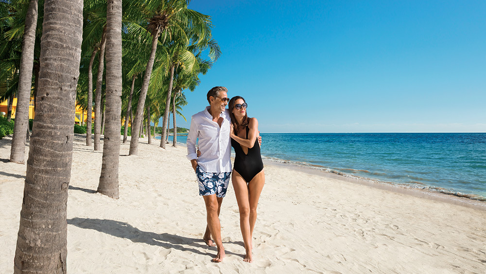 Couple walking on the beach at Zoetry Paraiso de la Bonita