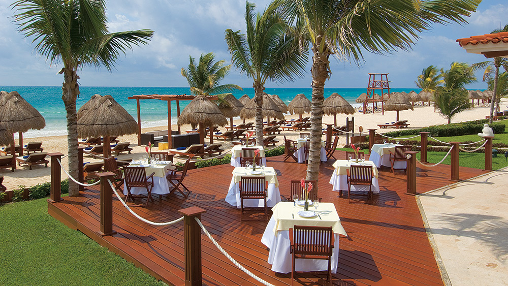 Outdoor dining area with beach views at Secrets Capri Riviera
