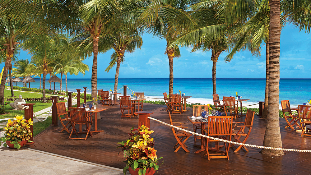 Outdoor dining area with ocean views at Secrets Capri Riviera