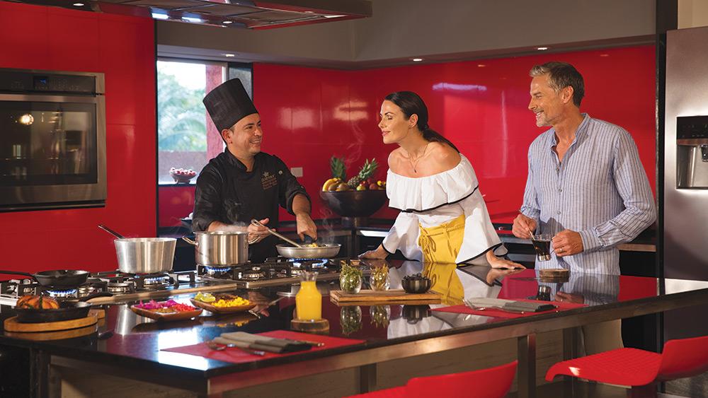 Couple with a chef in a cooking class at Zoetry Paraiso de la Bonita