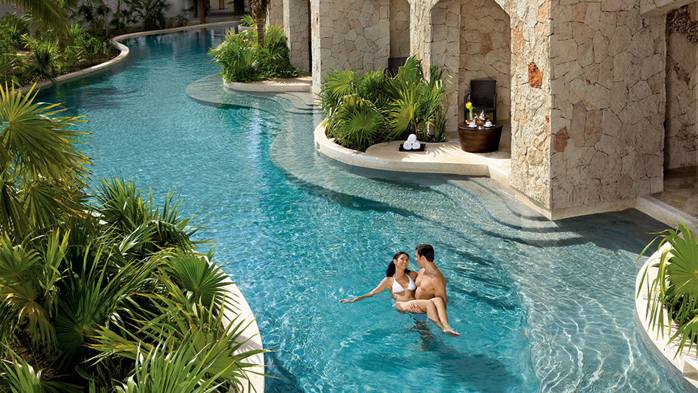 Couple swimming in a private pool in front of the swim up suites at Secrets Maroma Beach Riviera