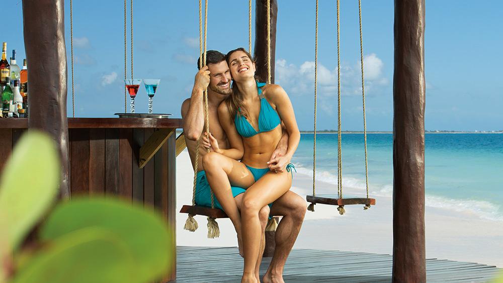 Couple on a swing at a beach bar at Secrets Playa Mujeres