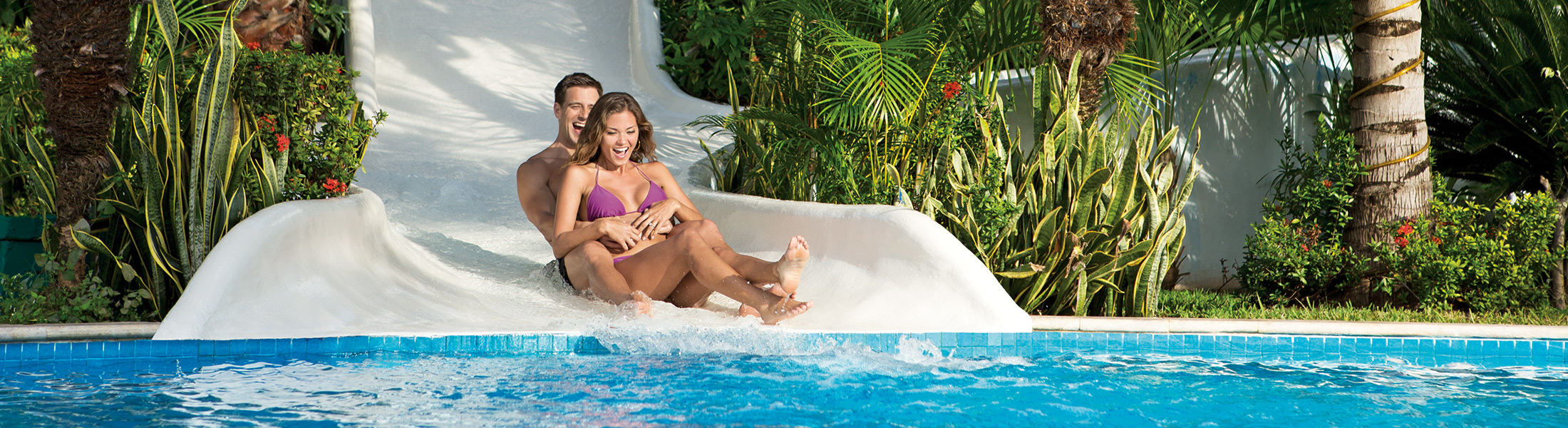 Couple sliding down a waterslide at Secrets Aura Cozumel