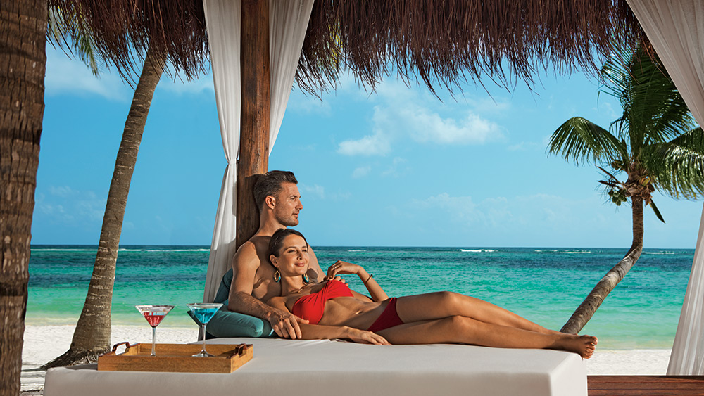 Couple relaxing on the daybed at the beach at Secrets Akumal