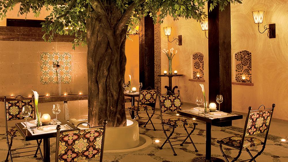 Outdoor dining courtyard in El patio Restaurant at Secrets Maroma Beach Riviera