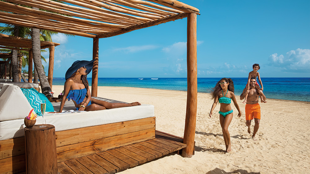 Family at the beach with a daybed at Dreams Punta Cana