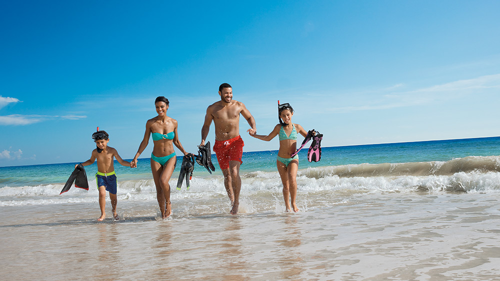 Family at the beach with snorkelling equipment at Dreams Punta Cana
