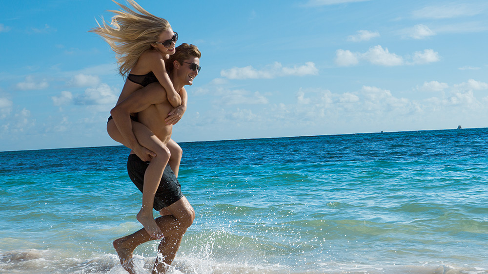 Man carrying a woman on the beach at Secrets Royal Beach
