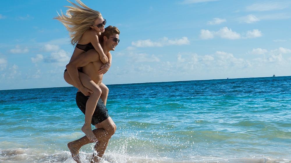 Man carrying a woman on the beach at Secrets Royal Beach