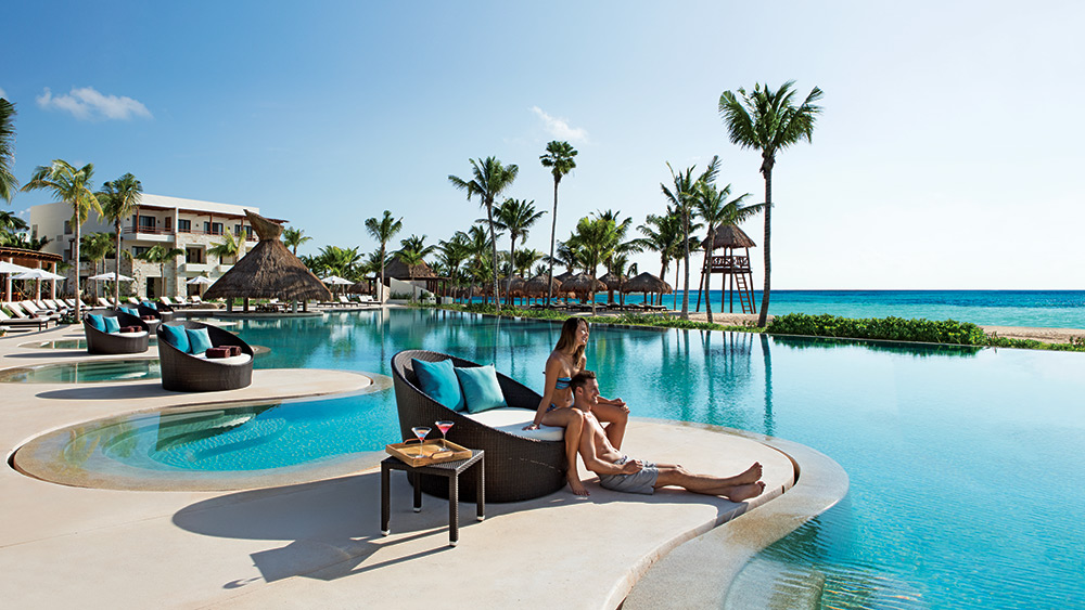 Couple on a sun lounger by the pool at Secrets Akumal