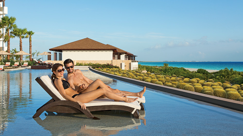 Couple on a sun lounger in a private pool at Secrets Playa Mujeres