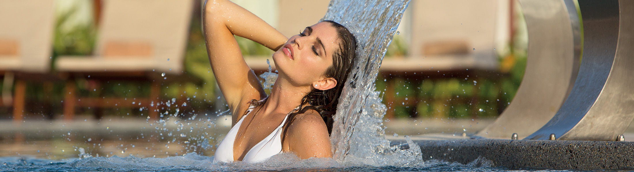 Woman under a waterfall in the spa at Secrets Playa Mujeres
