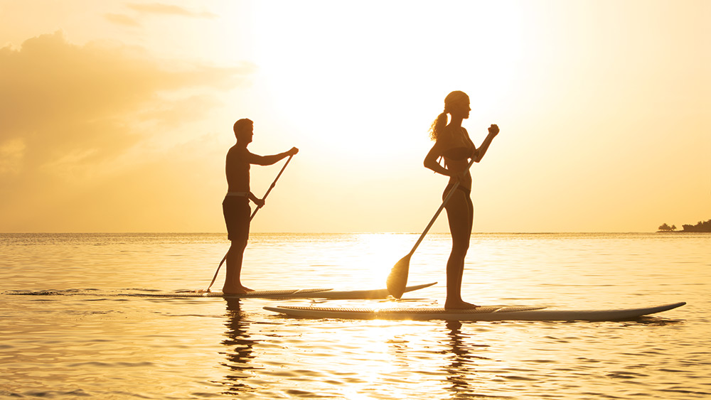 Couple on stand up paddleboards at sunset at Zoetry Montego Bay
