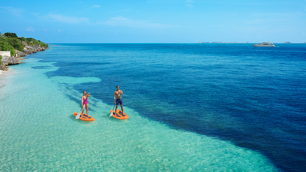 Couple paddleboarding at Zoetry Villa Rolandi Isla Mujeres