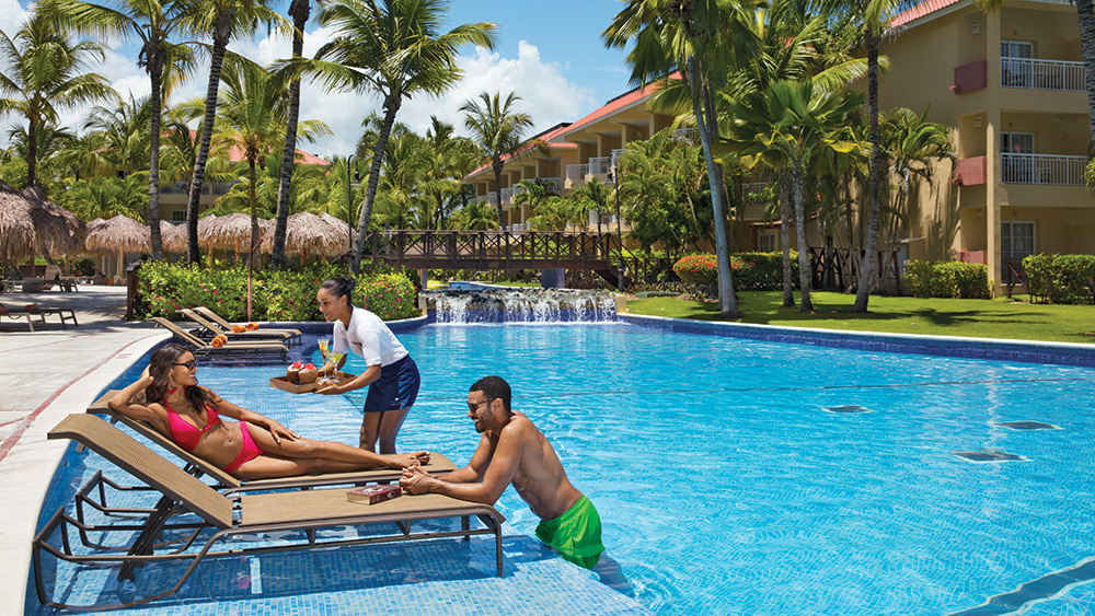 Couple being served drinks in the pool at Dreams Punta Cana